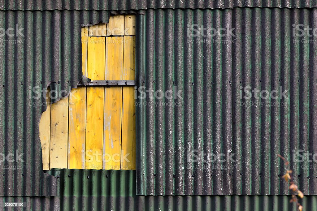 Wall of corrugated damaged asbestos material stock photo