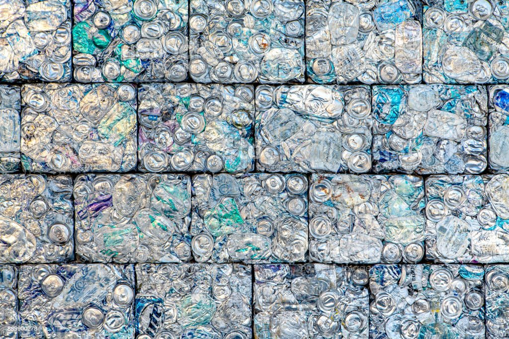 A wall of crushed aluminum cans recycled into building blocks stock photo