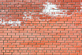 Wall of red brick, with white spots. The texture of the brickwork. Textured blank background.