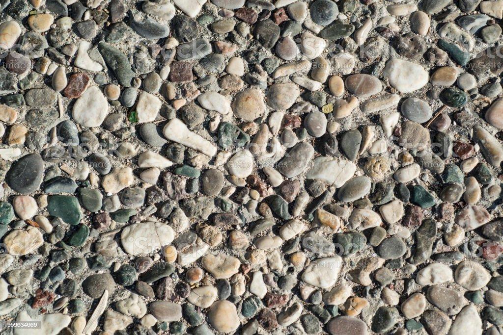 Pared de múltiples pequeños guijarros de color. La superficie de la piedra de la pared o la carretera. Fondo, textura. - Foto de stock de Adoquinado libre de derechos