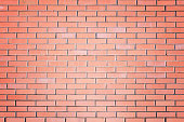 A wall of small red bricks. The texture of the brickwork. Strict empty background.