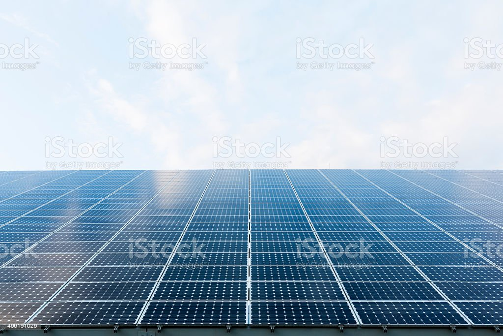 A wall of solar panels and blue sky stock photo