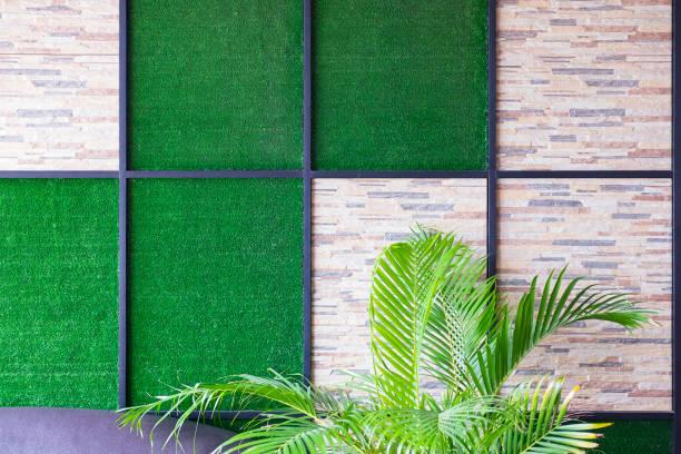 Duvar, taş ve metal çerçeve ve palmiye ağacı ile suni çim arka plan. stok fotoğrafı
