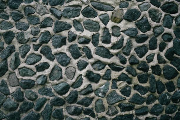 eine mauer aus ungleichmäßigen steinen - betonwerkstein stock-fotos und bilder