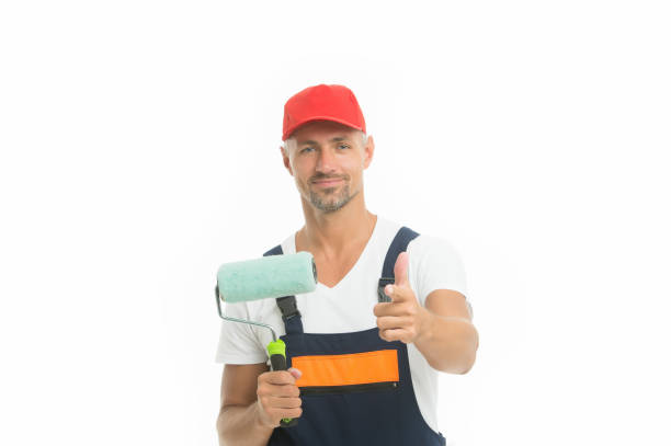 Wall painting is eco and economic. Paint rolling. Decorator hold paint roller. Wall painter. Paint work. Renovation and repair. Renewal and redecorating. Professional equipment. Mature man in cap stock photo