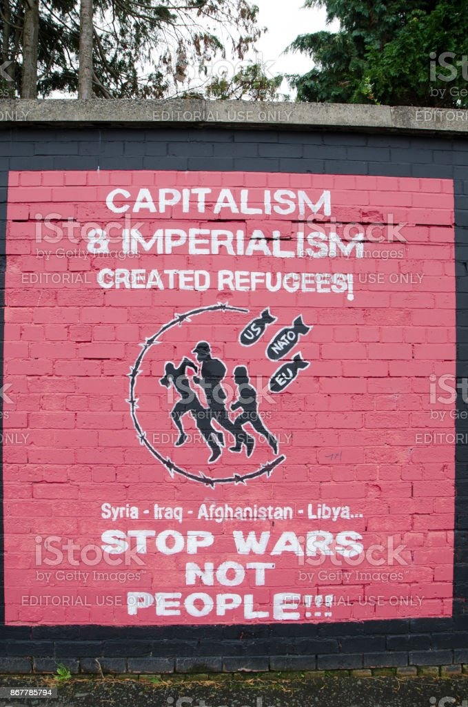 Wall painting mural against war, capitalism and imperialism in Belfast during day of autumn stock photo