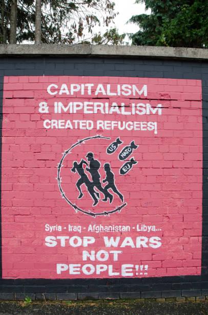 wandmalerei wandgemälde gegen krieg, kapitalismus und imperialismus in belfast tagsüber im herbst - imperialismus stock-fotos und bilder