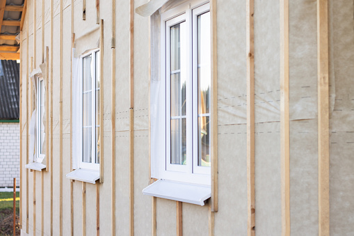 Wall, pediment of a house under construction with windows, vertical beams and a protective membrane, for wall cladding