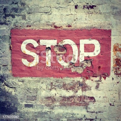 STOP painted on a very old brick wall