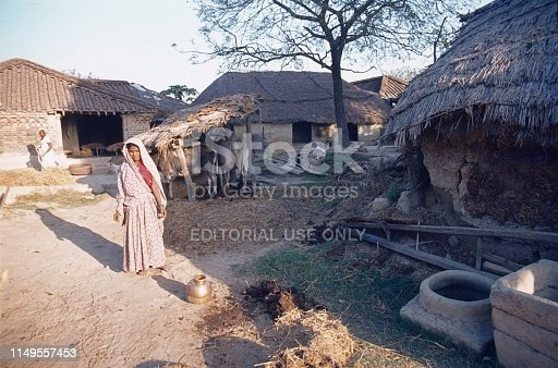 Nepal (exact location unfortunately not known), 1978. A female villager mends the façade of her hut with a cow pad-straw-sand mixture.