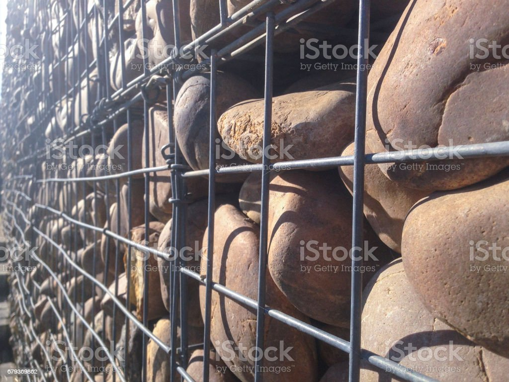 Wall protected with river pebble stones in iron mesh royalty-free stock photo