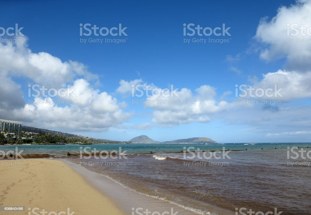 wall runs into the water at Kahala Beach stock photo