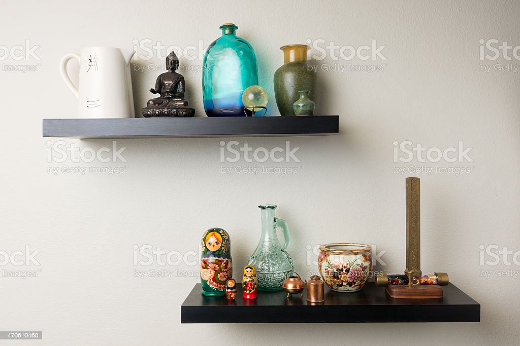 Home décor provided by a pair of shelves featuring a Buddha statue,...