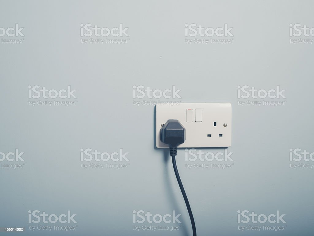 UK wall socket and cord on blue wall stock photo