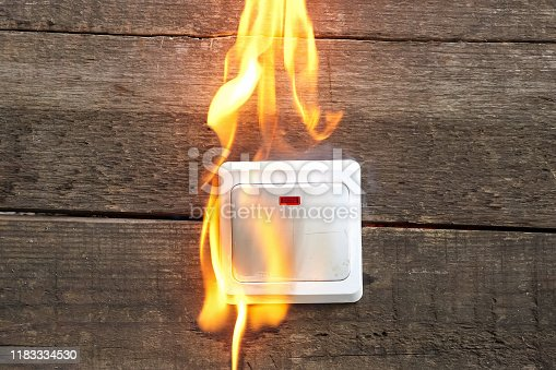1015605026 istock photo wall socket, smoke, fire occurred 1183334530