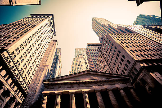 wall street in downtown manhattan with federal hall and skyscrapers - wall street lower manhattan stock pictures, royalty-free photos & images
