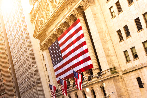 Wall street in New York Famous Wall street and the building in New York, New York Stock Exchange with patriot flag bailout stock pictures, royalty-free photos & images