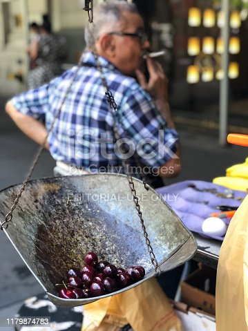 New York, USA - June 6, 2019: Fruit vendor on Wall Street in lower Manhattan late in the day selling cherries.