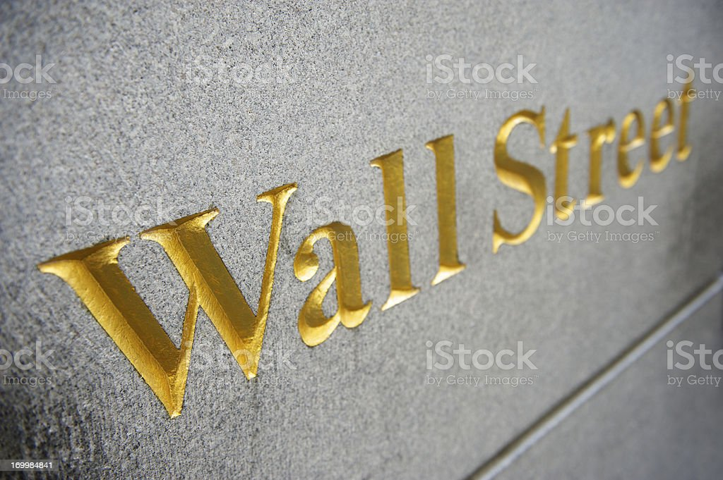 Wall Street Sign Etched in Gold on Gray Granite Background stock photo