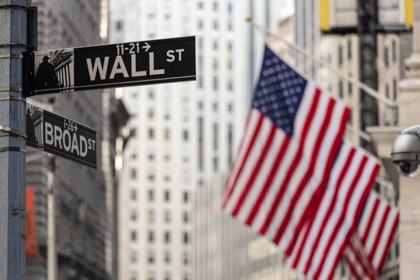 wall street sign in new york with american flags and new york stock exchange background. - wall street lower manhattan stock pictures, royalty-free photos & images