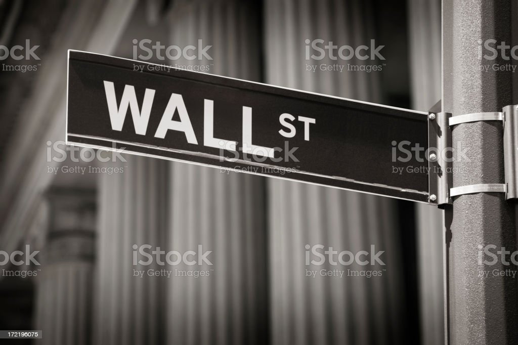 Wall Street Sign Wall St. street sign with financial institution behind it Business Stock Photo
