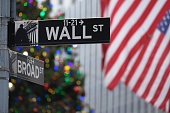 Wall Street sign in New York with American flag and Christmas tree lights in the background.