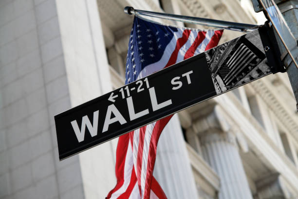 wall street sign with us flag behind - wall street lower manhattan stock pictures, royalty-free photos & images