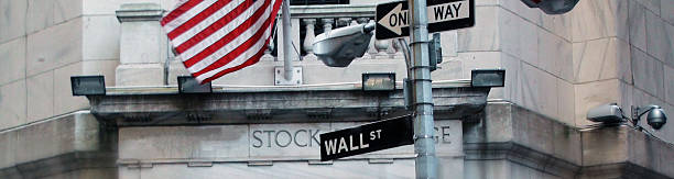 wall street sign with us flag in new york city - new york stock exchange stock pictures, royalty-free photos & images