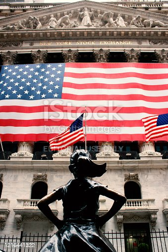The fearless girl stands facing the Stock Exchange American flag. Wall Street in the Financial District in Lower Manhattan of New York City closed and vacant of people and reported during the COVID-19 breakout caused by the coronavirus pandemic.