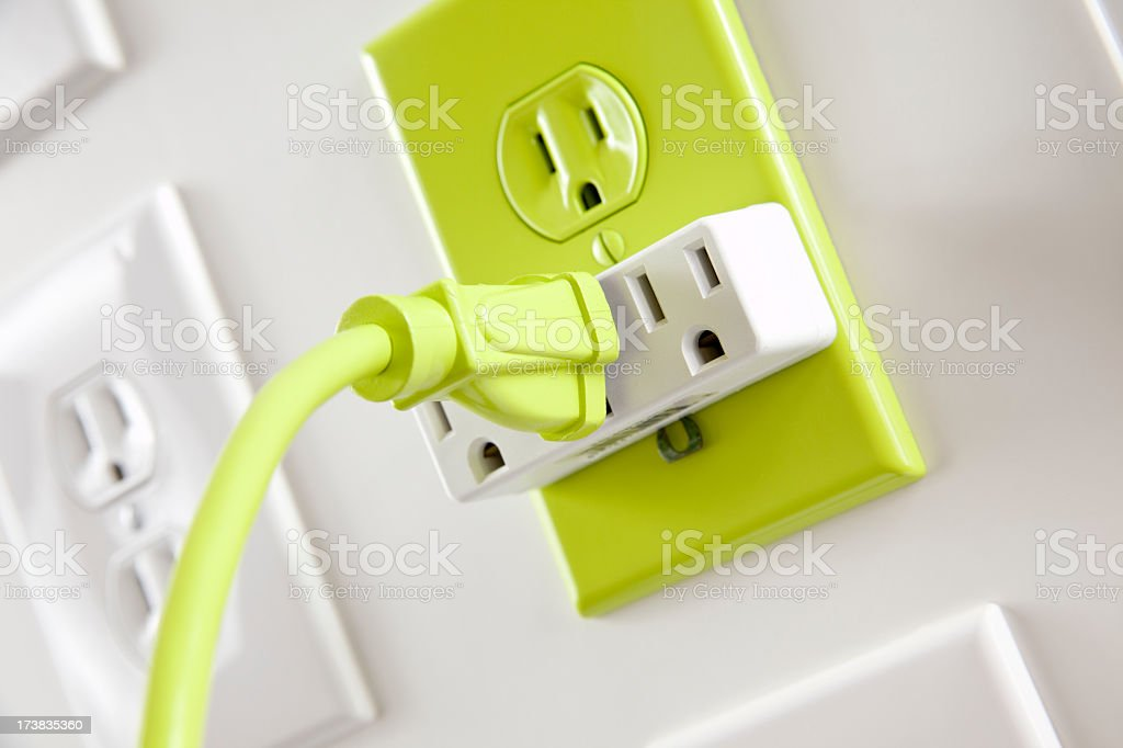 Wall  white electrical plugs with one green cord and outlet stock photo