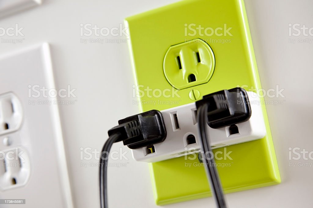 Wall  white electrical plugs with one green cord and outlet royalty-free stock photo