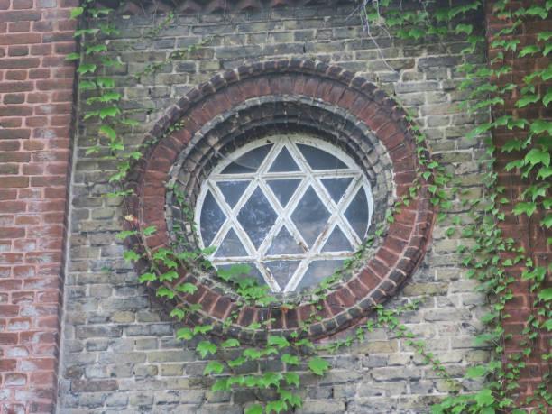 muur met een ronde zes puntige ster gevormd venster en Ivy groeien foto