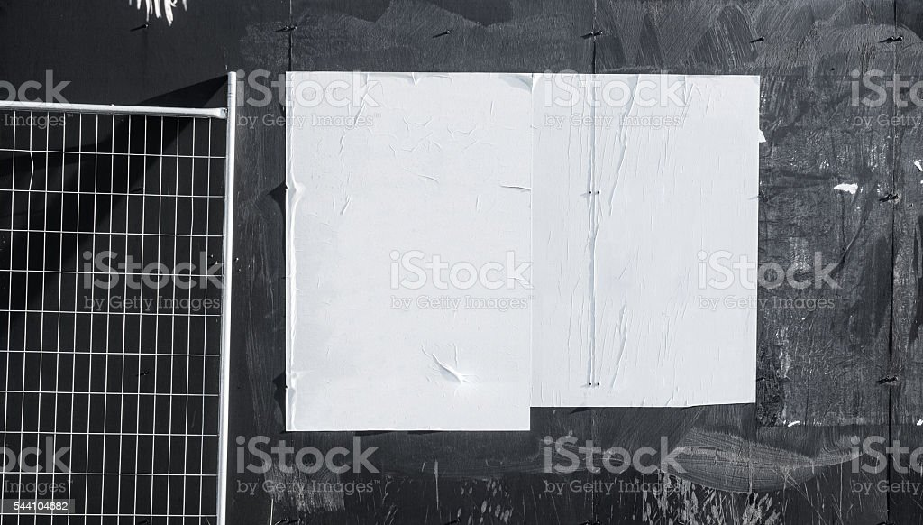 Wall with blank poster and torn posters - Photo