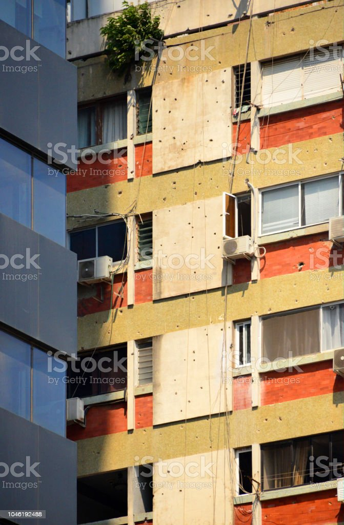 Wall with bullet holes from the civil war, next to a new building, Luanda, Angola stock photo