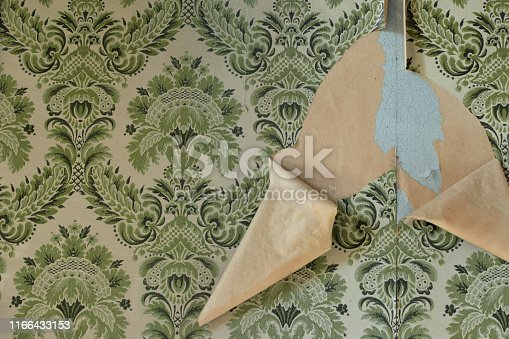 Wall with torn wallpaper in old house. Vintage background pattern.
