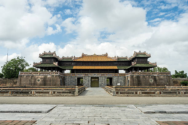Walled fortress entrance to Hue Imperial City, Vietnam. Symmetrical frontal view with cobble stone ground and cloudy blue sky. huế stock pictures, royalty-free photos & images