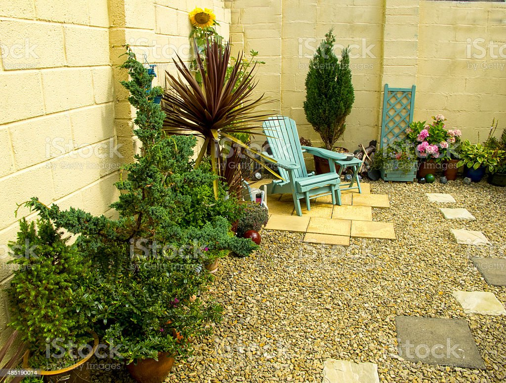 Walled garden with small trees and wooden chair stock photo