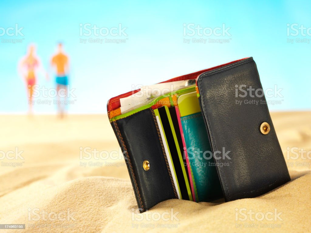 Wallet in the Sand with Background People stock photo