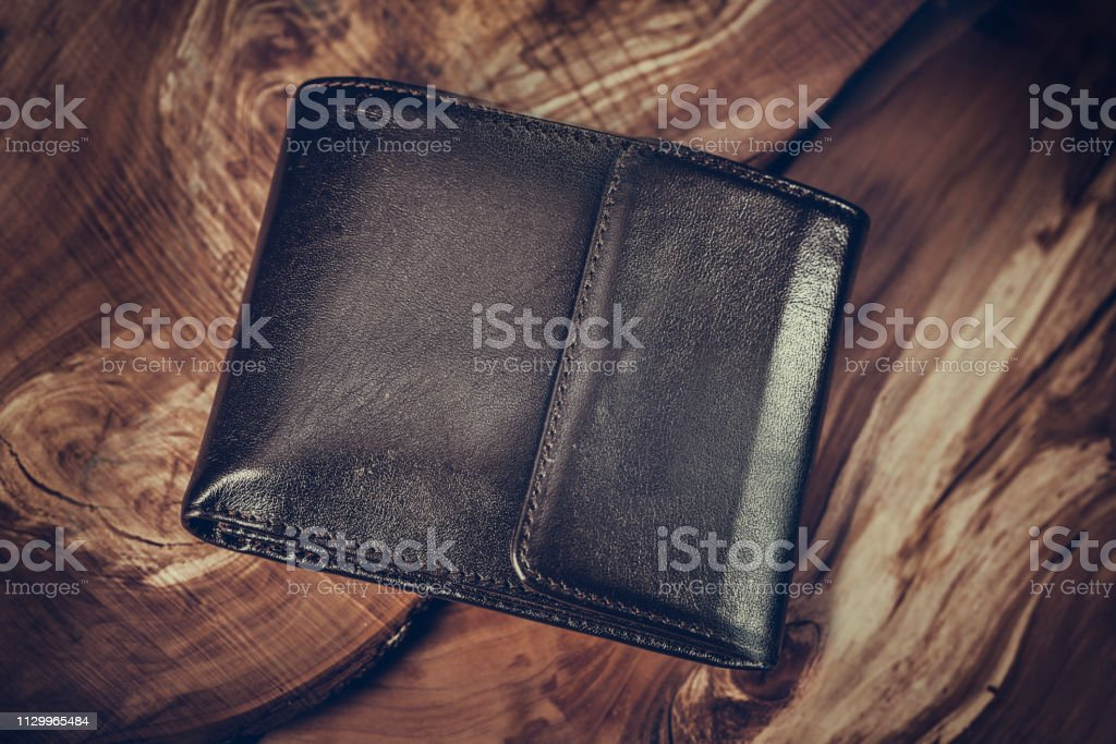 Brown wallet on wooden texture background