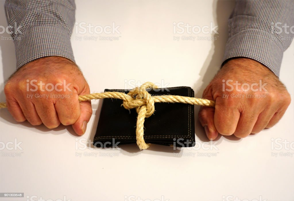 A wallet tied with a rope, in a man's hand stock photo