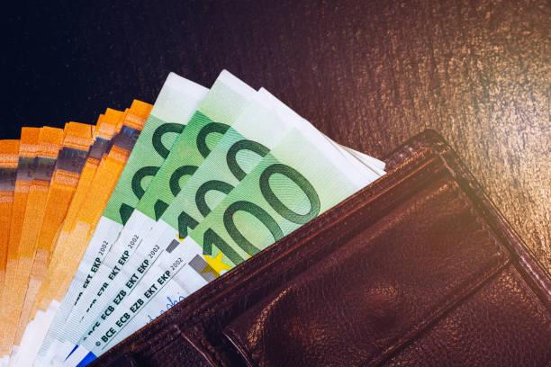 Geldbörse mit Euro-Banknoten. Bargeld im Portemonnaie auf schwarzem Hintergrund. Euro-Geld in Ledertasche. – Foto