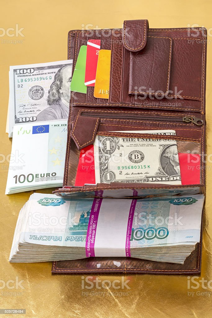 Wallet filled with paper money and credit cards on a gold background