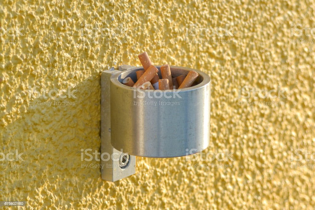 Wall-mounted stainless steel cigarette bin on an exterior wall outside a place of work where smoking is banned inside. This enables smokers to extinguish and dispose of cigarettes. stock photo