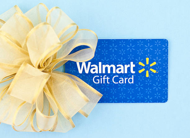 WalMart Gift Card with Bow Suffolk, Virginia, USA - May 2, 2011: A horizontal studio shot of a WalMart gift card and a gold bow photographed on a blue background. wal mart stock pictures, royalty-free photos & images