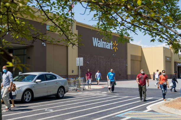 walmart line outside the store with masked people practicing social distancing 6 feet apart during covid-19 corona virus pandemic. - walmart стоковые фото и изображения