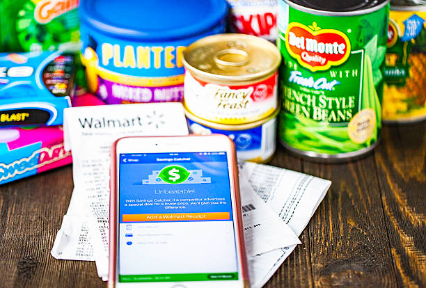Walmart Savings Catcher App on iPhone screen and assorted groceries Peyton, Colorado, USA - August 30, 2016: A horizontal studio shot of an Apple iPhone 6 plus with the Walmart Savings Catcher app on the screen. Behind the phone are receipts from Walmart and an assortment of groceries purchased at the store. wal mart stock pictures, royalty-free photos & images