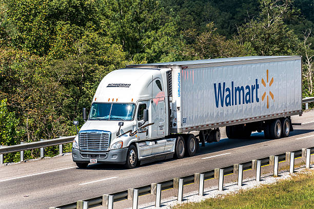 "Walmart Semi-Truck Traveling On The Interstate ""Knoxville, Tennessee, USA - September 14, 2011: A Walmart delivery truck travels between stores making deliveries.  Walmart is a huge chain of grocery, department and warehouse stores based in Bentonville, Arkansas, USA and founded by Sam Walton in 1962."" wal mart stock pictures, royalty-free photos & images"