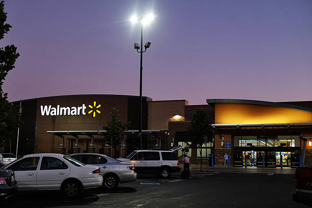 Wal-Mart Twilight Folsom, California, USA - August 13, 2016: Approaching entrance of Walmart Superstore in Folsom, California, at twilight hour while customers are going in and out of the store.  wal mart stock pictures, royalty-free photos & images
