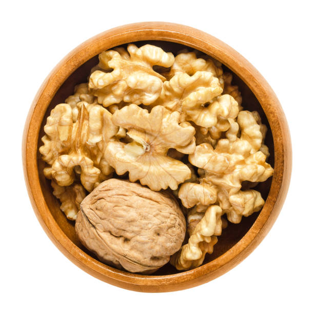 Walnut and shelled walnut kernel halves in wooden bowl Whole walnut and shelled walnut kernel halves in wooden bowl. Seeds of the common walnut tree Juglans regia. Snack or used in bakery. Isolated macro food photo close up from above on white background. walnut stock pictures, royalty-free photos & images