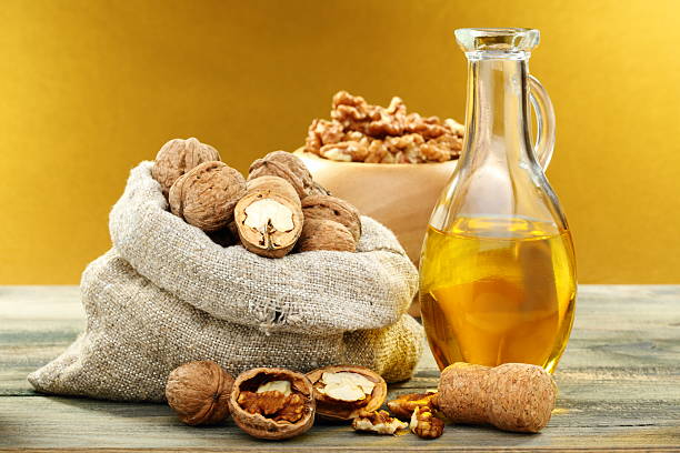Walnut oil in bottle and nuts. stock photo